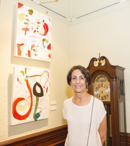 Anne Brilliant in front of her two paintings in the Studioeleven exhibit at the Ebell (photo by
